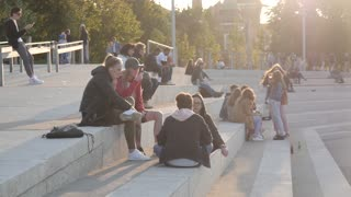 Young People relax sitting on the Stairs in the City Park, evening Sun