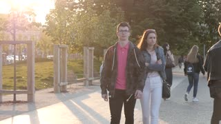 Young People students couple walking in the City Park, evening yellow Sun