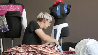 Young Tailor Working In Fashion Design Studio with new Collection on Mannequins