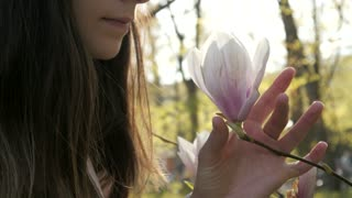 Young Woman sniffing Flower of Magnolia in a Spring Park