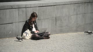 Young woman work with laptop sitting on pavement on the street in the city Paris