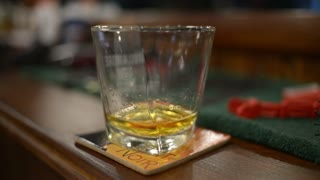 whiskey is on the table - the man's hand taking a glass - close-up