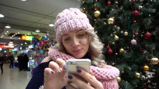 Woman Blonde chatting having fun wia Mobile Phone on Christmas Fair Tree in Mall