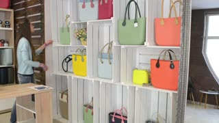 Woman brunette get shopping at store, clutches, bags, handbags on shelf