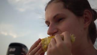 Woman eating corn - picnic outdoors