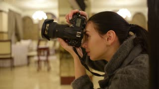 Woman Fashion Photographer works with Camera at the Studio
