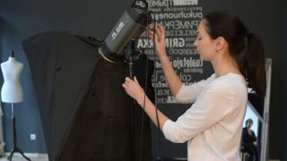 Woman Fashion Photographer works with Flash at the Studio