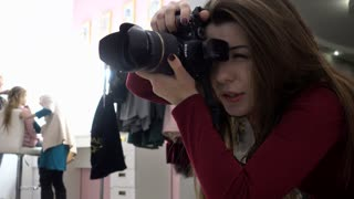Woman Fashion Photographer works with Model at the Studio