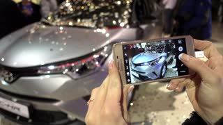 Woman Taking photo by Mobile Phone of New Toyota car presentation