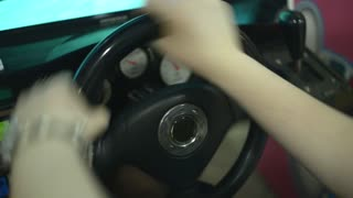 Woman's hands turn the steering wheel in racing simulator