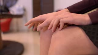 Women's fingers tapping on the bare knees