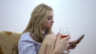 Young Blonde Woman Chatting with Mobile phone, Drinking Wine alone, Sitting On Sofa