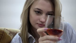 Young, Blonde Woman Relaxing And Drinking Beverage Wine On Sofa in white room