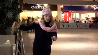 Young Blonde Woman trying to ride on Skates on Ice on Christmas Fair
