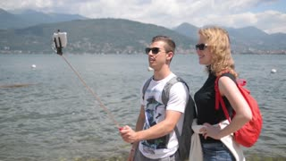 Young boy and girl doing the selfie photo against the Lago Maggiore in the Alps