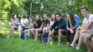 Young Catholic sing and clap their hands at a picnic nature