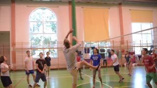 Young Catholics play a friendly game of volleyball in the gym of the school