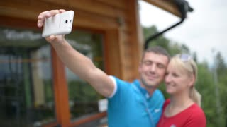Young couple kiss and take selfie photos via Mobile Sell Phone and kisses