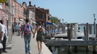 Young Couple walk by Embankment and pier in Venice and parked gondolas