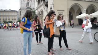 Young female tourists with maps and mobile phones in the center of the old town