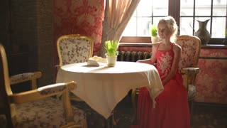 Young girl in elegant dresses sitting waiting at a table in a restaurant