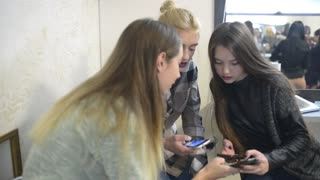 Young girls with their Smartphones and mobile phone chatting in Beauty salon
