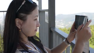 Young Korean girl take photo with Mobile Sell Phone on Green Nature