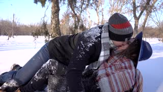 Young man and woman love, kissing romantic having fun in the winter day park falling on snow