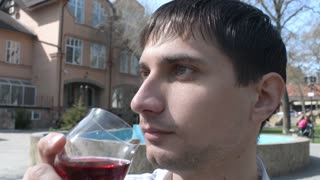 Young Man drinks red wine on the street of an old Europe town