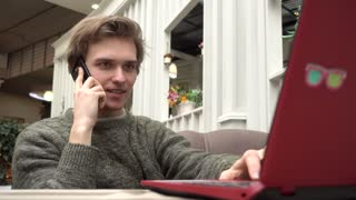 Young Man freelance outsource work Using Laptop In Cafe, Talking On Smartphone