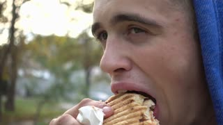 Young Man Teenager eating Doner Kebab at the City Park - Autumn Day