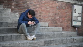 Young Man with mobile sell Phone on the steps of the fountain Sisto Rome Italy