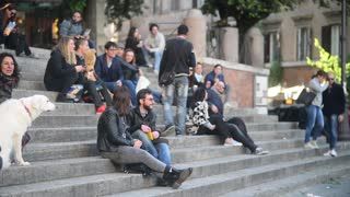 Young People relax and communicate on the steps of the fountain Sisto Rome Italy