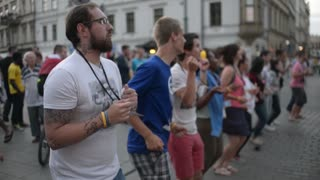 Young people tourists dancing synchronously in Krakow street evening