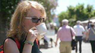 Young sexy blonde drinking coffee on the streets of the old Italian town