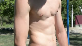Young sexy guy shows his strong abdominal muscles during exercise