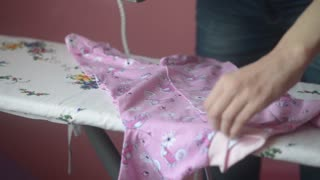 young woman ironing baby clothes on an ironing board at home