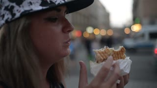 Young woman tourist eating Doner Kebab at the night street Krakow - close up