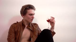 Young drunk Handsome Man Guy alone Drinking Beverage Wine sitting in ampty room