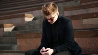 Young Man in a black Coat Chatting with Mobile Smart Phone in the City Kiev, Day