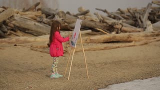 child paints on an easel on the beach