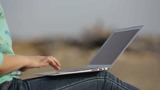 girl working on laptop on beach closeup