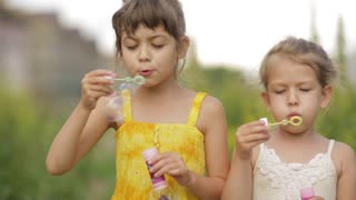 little girl blowing soap bubbles in summer park