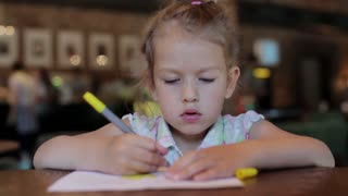 little girl draws in the cafe waiting for the order. child in restaurant
