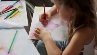 little girl draws with crayons sitting at table. close up