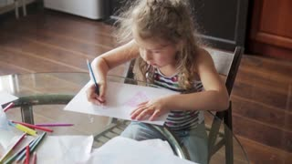 little girl draws with crayons sitting at table