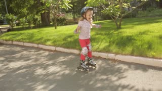 little girl learns to roller skate in the Park