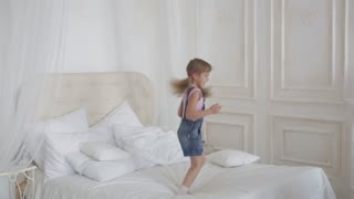 little girl playing and jumping on the bed