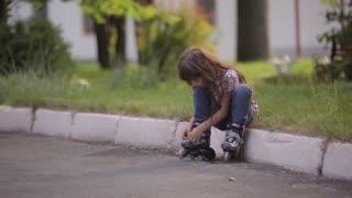 little girl puts on roller skates in the Park