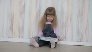 little girl reading a book sitting on floor